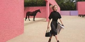 Młoda dziewczyna ubrana w czarną sukienkę, trzyma niewielką torbę. Za nią widać różową ścianę i czarnego konia.