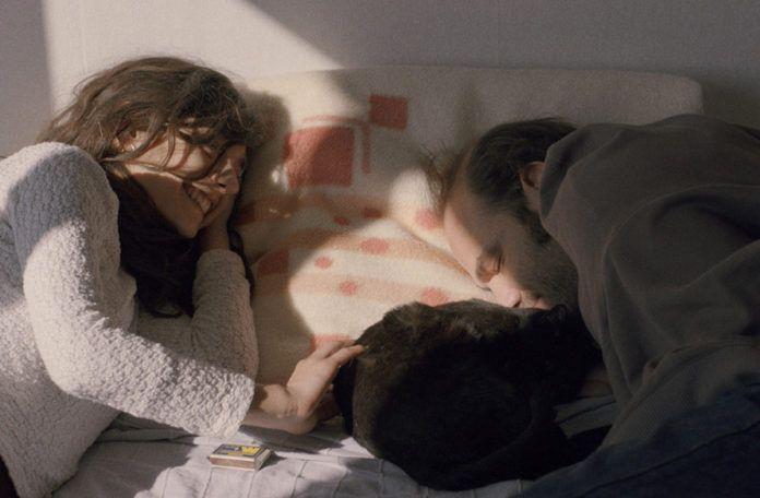 para leżąca na łóżku z kotem