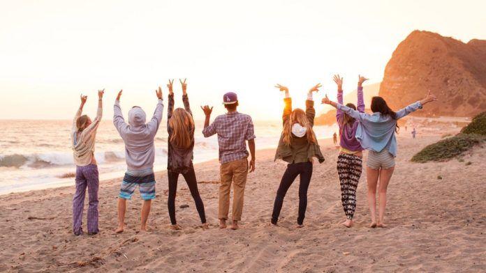 przyjaciele na plaży, stoją tyłem do zdjęcia, morze, słońce