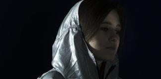 Kobieta w srebrnym, ortalionowym płaszczu z kapturem