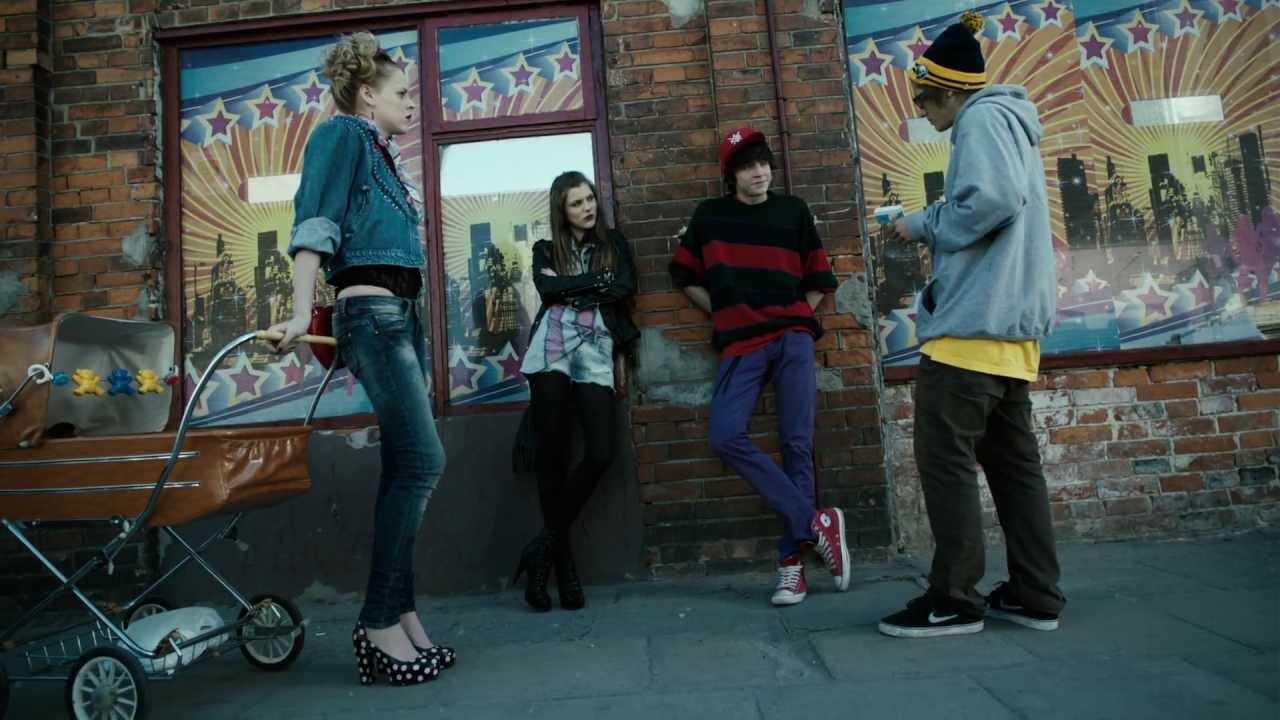 Czworo młodych ludzi stoi na tle ściany, jedna z dziewczyn stoi przy wózku dla dzieci