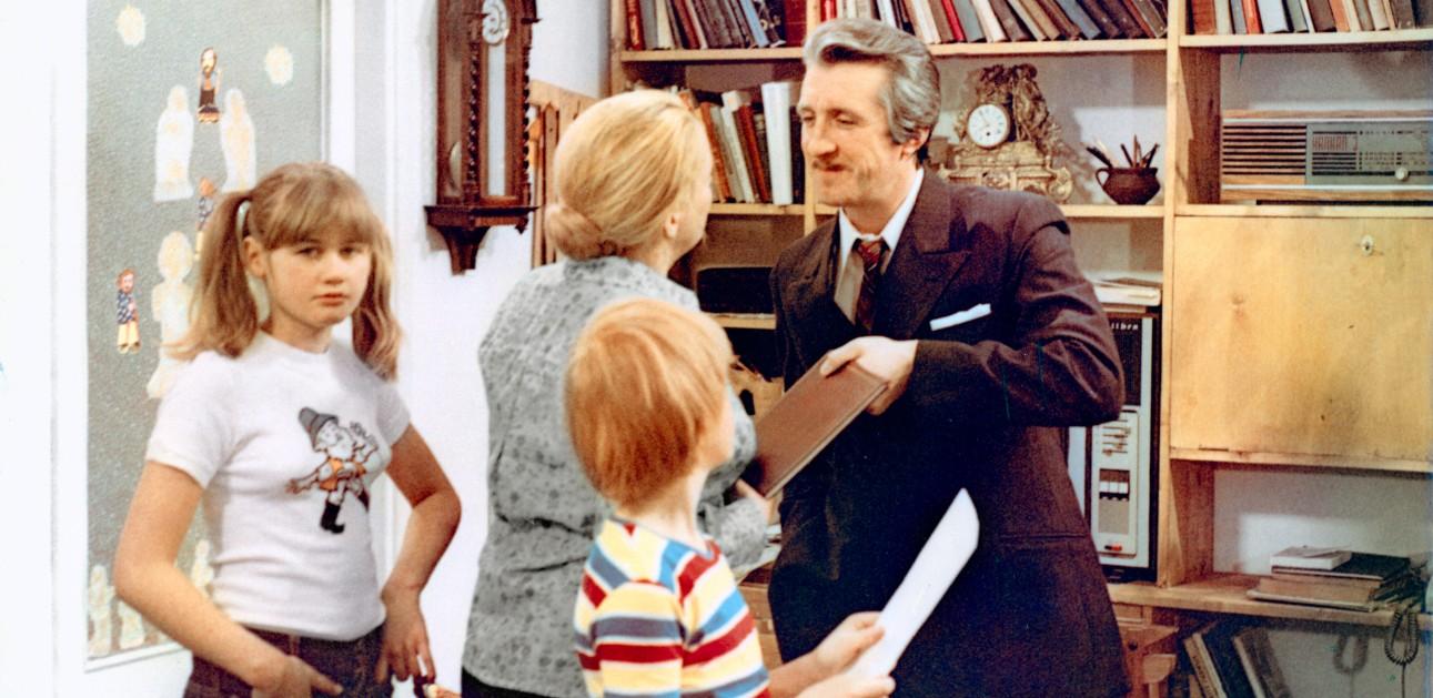 Mężczyzna w garniturze, kobieta z kokiem i rudy chłopiec w bluzce w paski