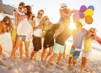 grupa ludzi na plaży z balonami