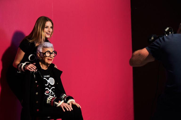 Starsza kobieta siedzi, za nią stoi młoda dziewczyna pozują do zdjęcia