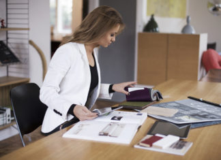 Kobieta w białej marynarce czyta coś przy biurku