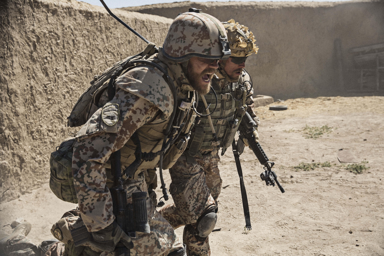 Kadr z filmu Wojna, dwóch żołnierzy niosących innego żołnierza, teren pustynny