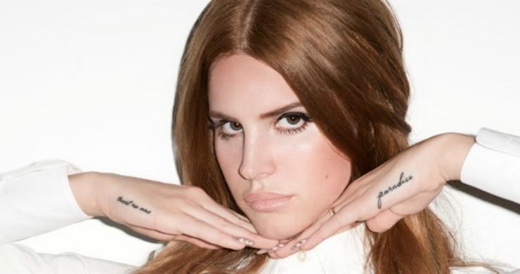 Lana Del Rey na białym tle w białej koszuli, trzymająca ręce pod brodą pokazująca tatuaże