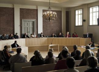 Sala sądowa pełna ludzi ubranych na czarno