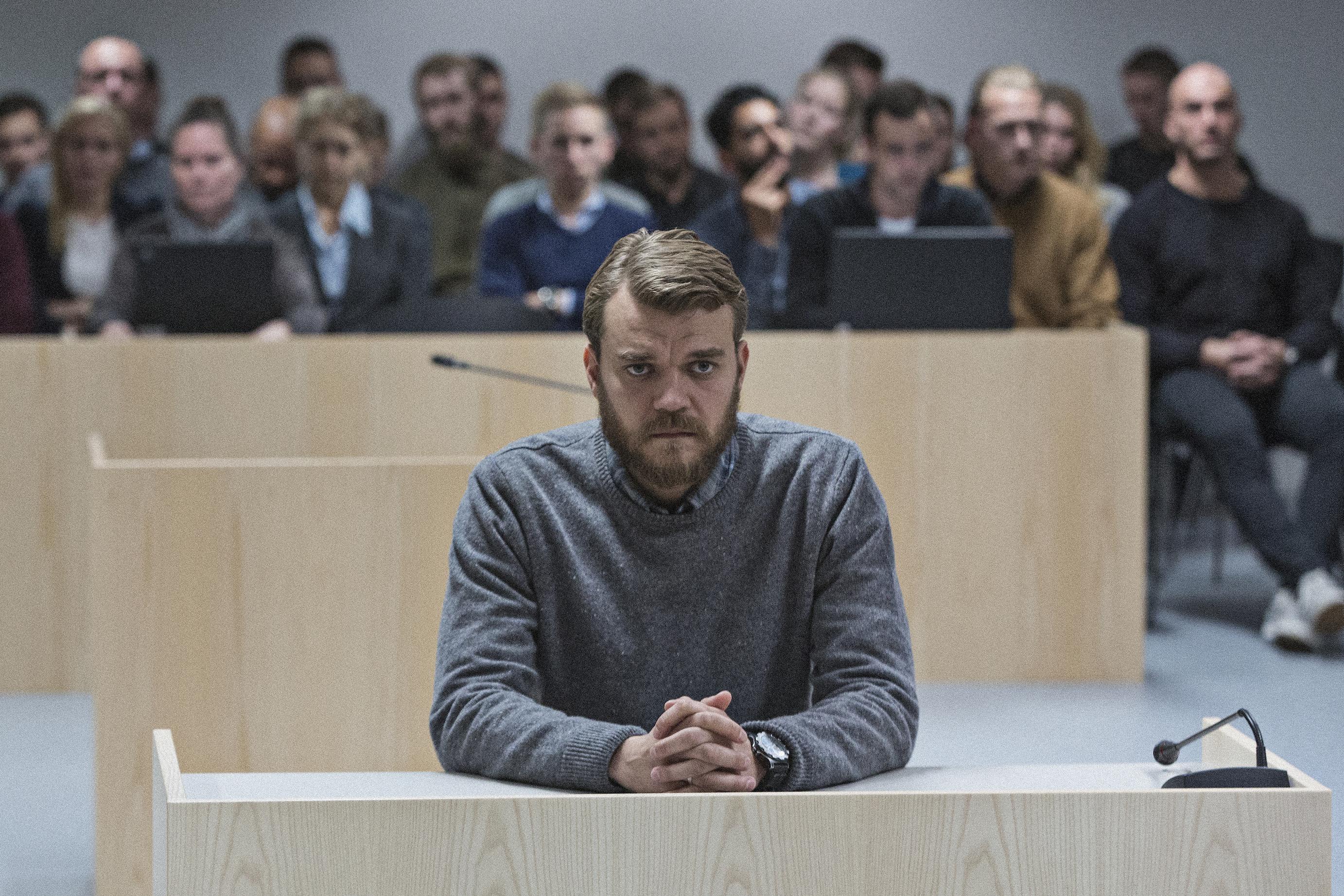 Kadr z filmu wojna, mężczyzna ok 30/40 letni siedzący na sali sądowej