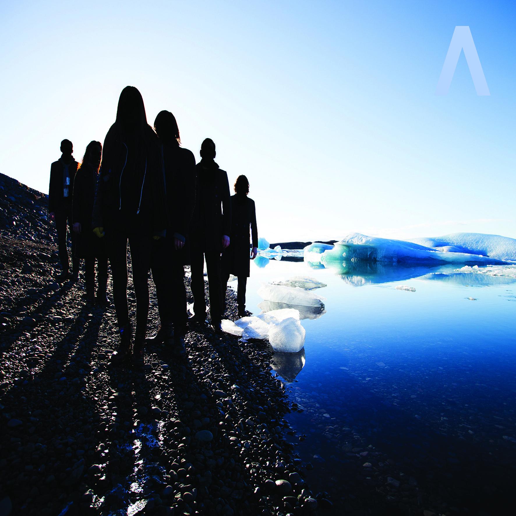 Grupa ludzi ubranych na czarno stoi obok niebieskiej wody
