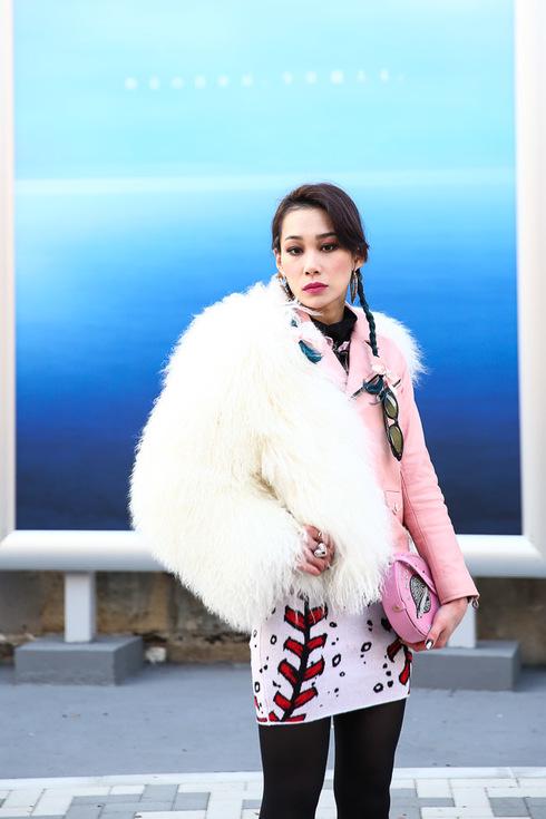 Kobieta w biało-różowym futrze na niebieskim tle