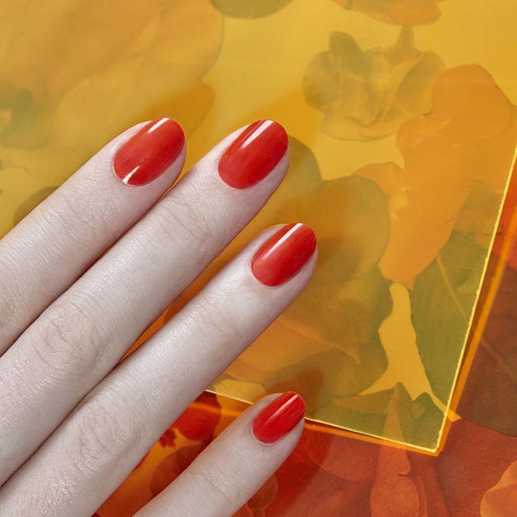kobiece palce z umalowanymi paznokciami w kolorze pomarańczowym