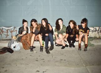 Kilka dziewczyn ubranych na ciemno siedzących na betonowym placu