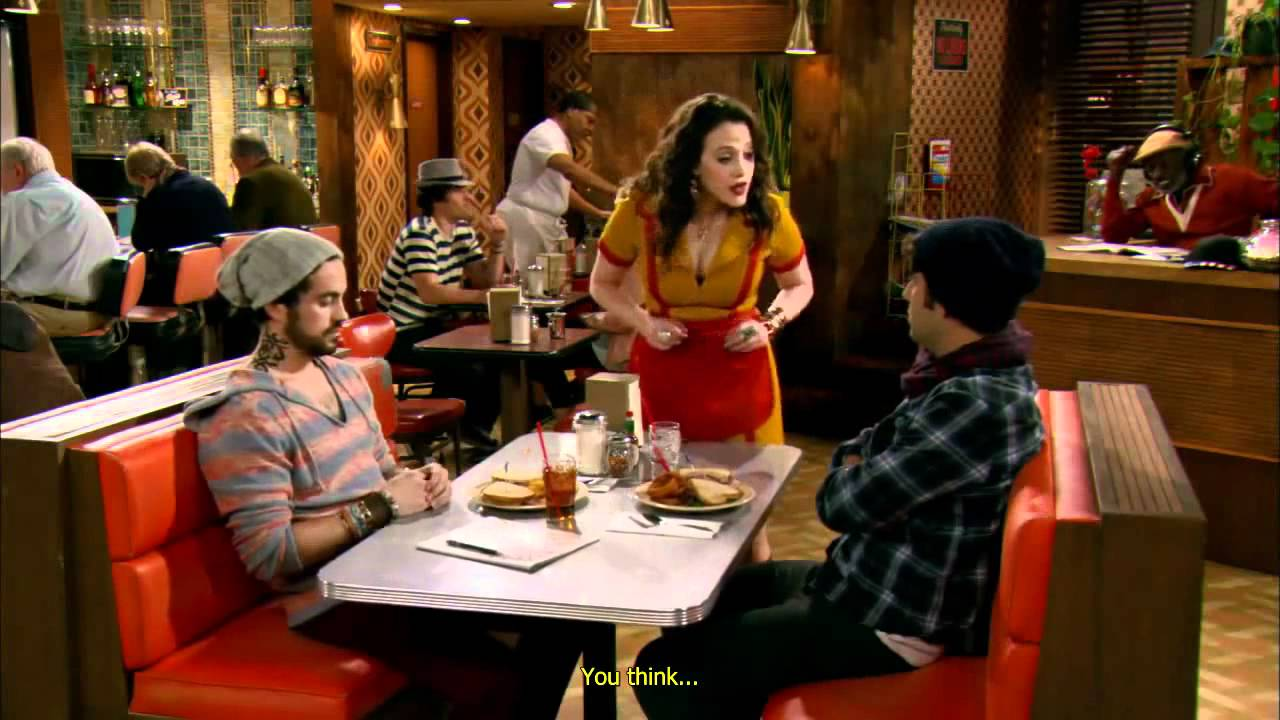 Kobieta z ciemnymi włosami i dwóch mężczyzn rozmawiają w barze