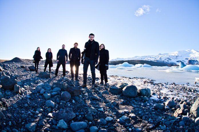 Grupa ludzi ubranych na czarno na tle skalistej plaży
