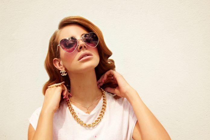 Lana Del Rey w okularach-serduszkach i złotym kajdanie na tle ściany