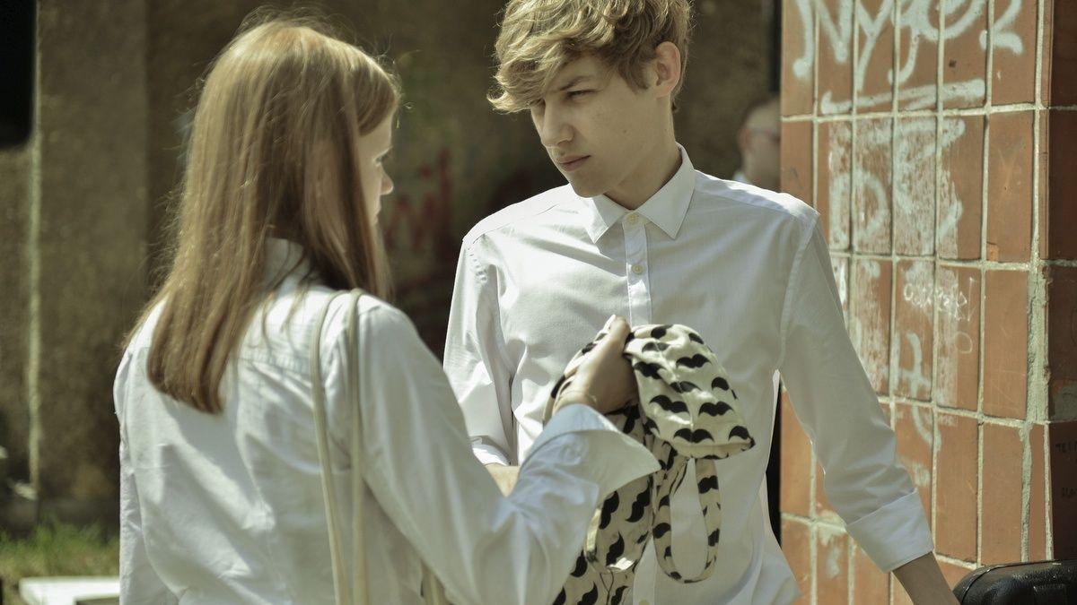Dwoje nastolatków stoi na dworze, są ubrani na galowo