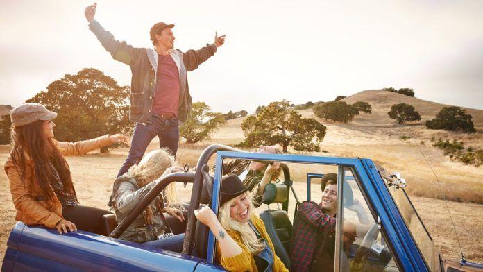 Grupa ludzi ubranych na kolorowo jadących samochodem przez sawannę