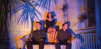 Kobieta wi dwóch mężczyzn siedzi na wielkim tronie, palmy
