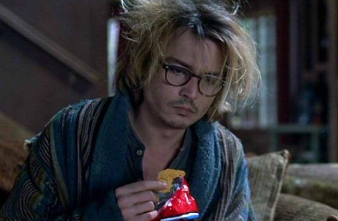 Mężczyzna z potarganymi włosami siedzący na kanapie i jedzący chipsy