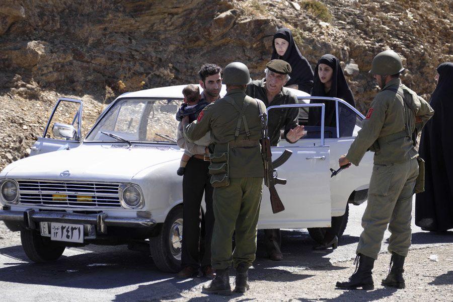 Ludzie wysiadający z samochodu, wokół nich stoją żołnierze