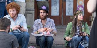 Grupa hipsterów siedzi na ulicy i je