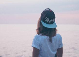 Dziewczyna w czapce z daszkkiem i białej bluzce stoi odwrócona w stronę morza