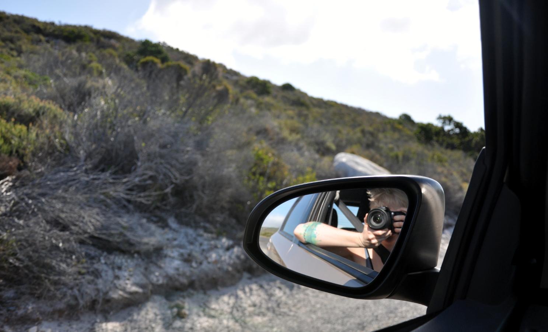 Zbocze, lusterko samochodu i blondynka robiąca zdjęcie