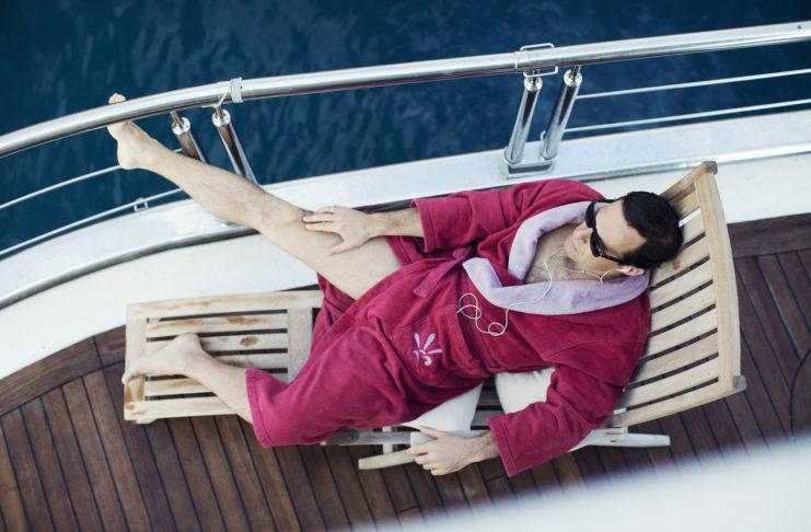 Mężczyzna w różowym szlafroku na leżaku na jachcie