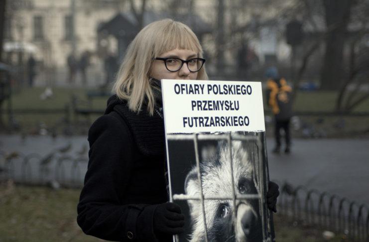 """Blondynka w ciemnych płaszczu trzyma transparent z lisem i podpisem """"Ofiary polskiego przemysłu futrzarskiego"""""""