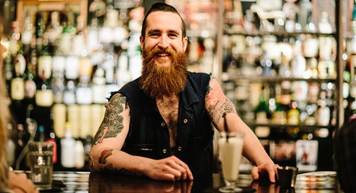 Barman z brodą i tatuażami