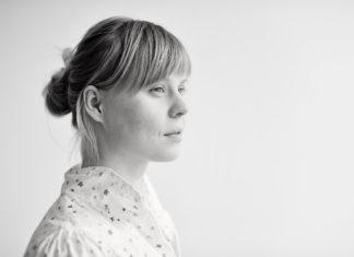 Kobieta w związanych włosach i jasnej bluzce patrzy przed siebie