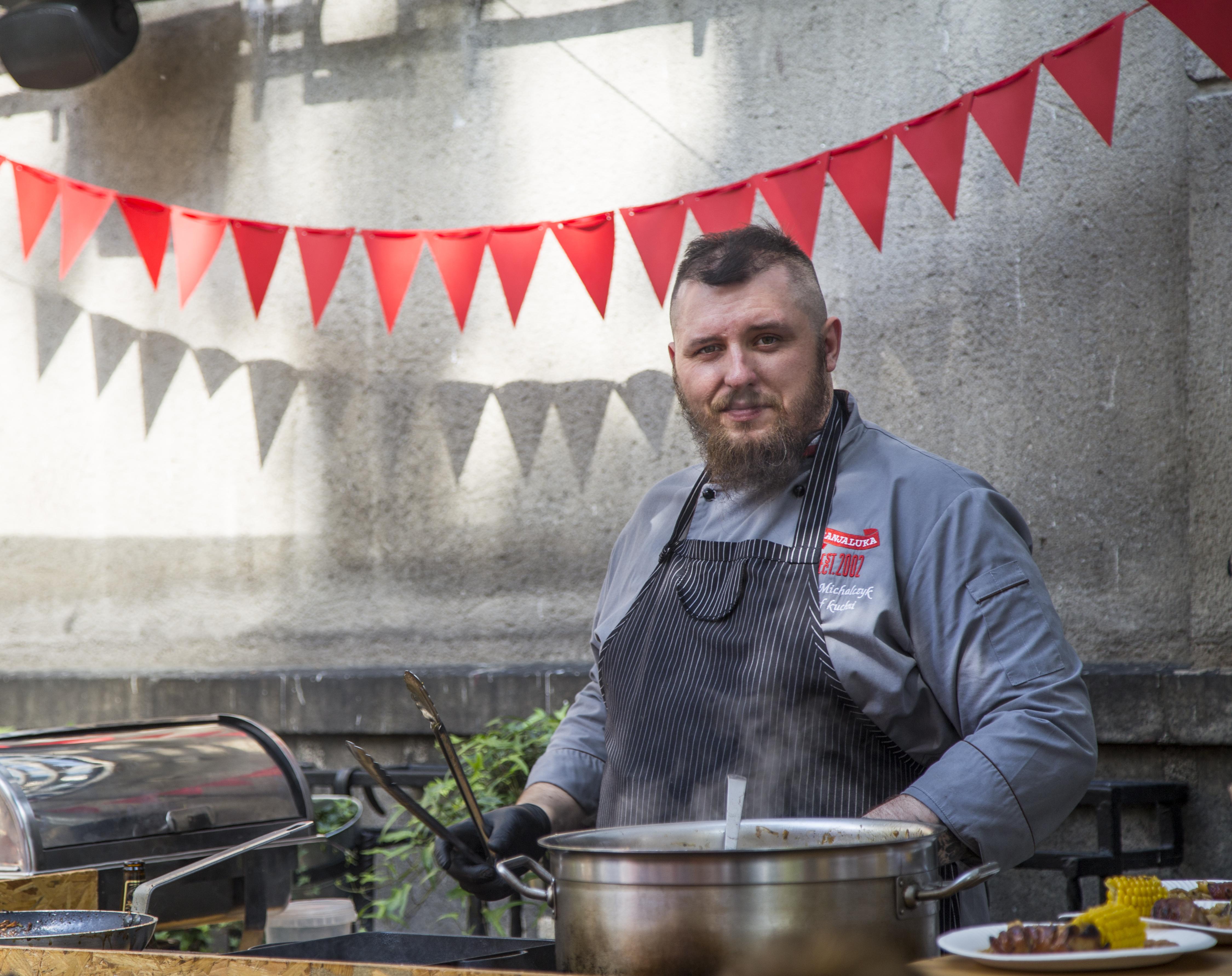 Kucharz w fartuchu stoi przy garnku