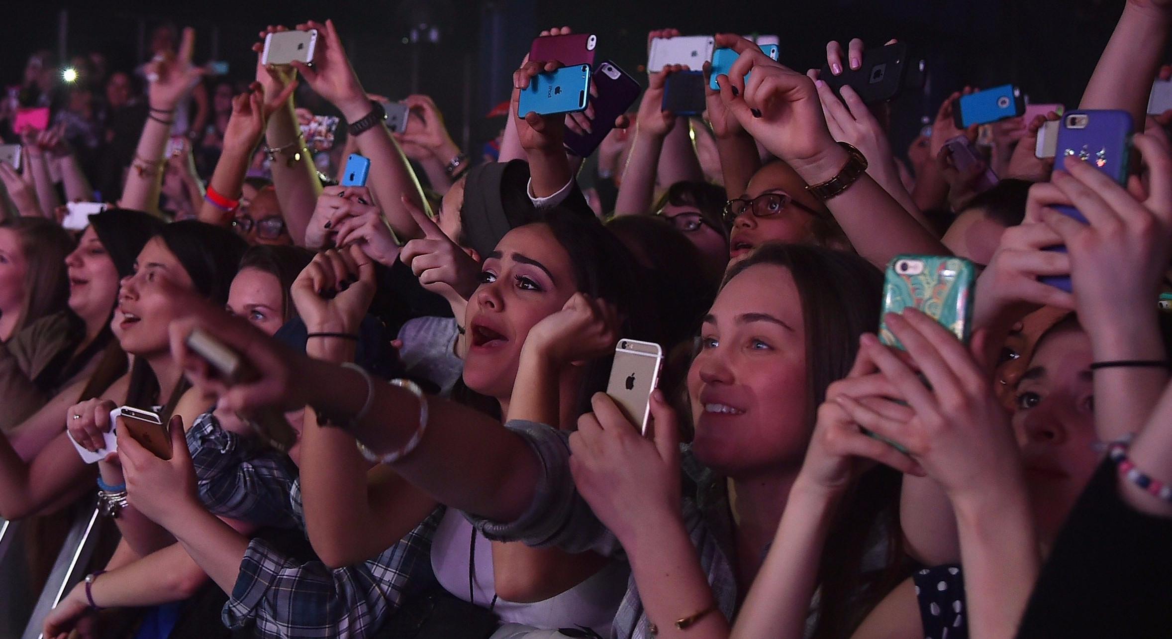 Grupa ludzi przed sceną z telefonami