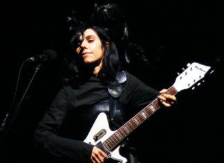 Brunetka z czarnym pióropuszem i białą gitarą