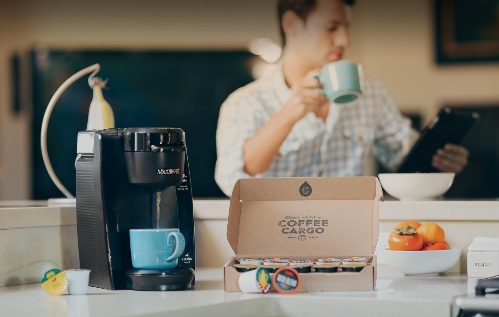 Pudełko subskrypcyjne, czarny ekspres do kawy, w tle mężczyzna z kubkiem
