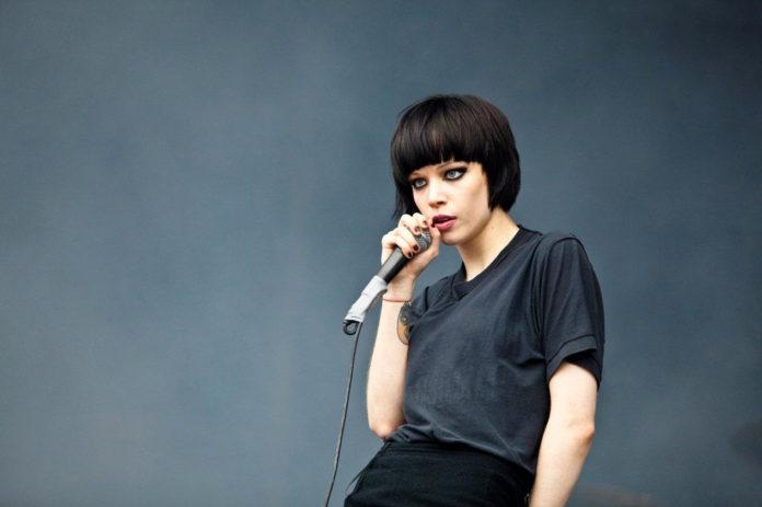 Brunetka z krótkimi włosami w ciemnej bluzce śpiewa do mikrofonu