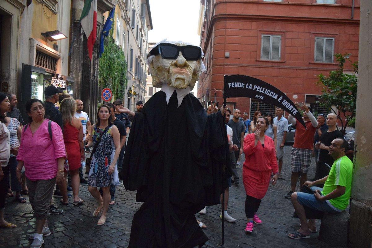 Kukła w czarnej pelerynie z kosą i w ciemnych okularach
