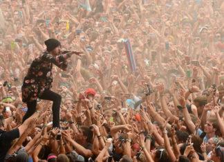 Piosenkarz wykonuje utwór stojąc na rękach publiczności