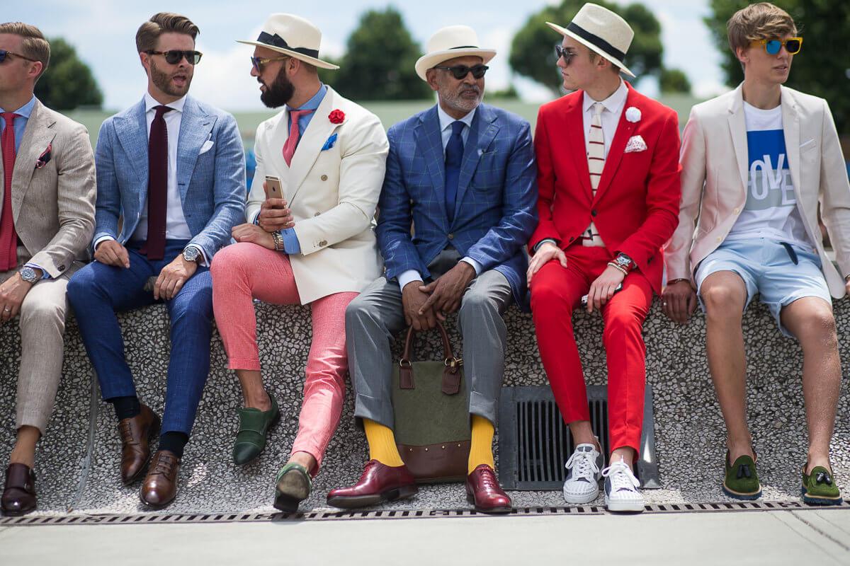 Grupa facetów w kolorowych garniturach siedzi na murku