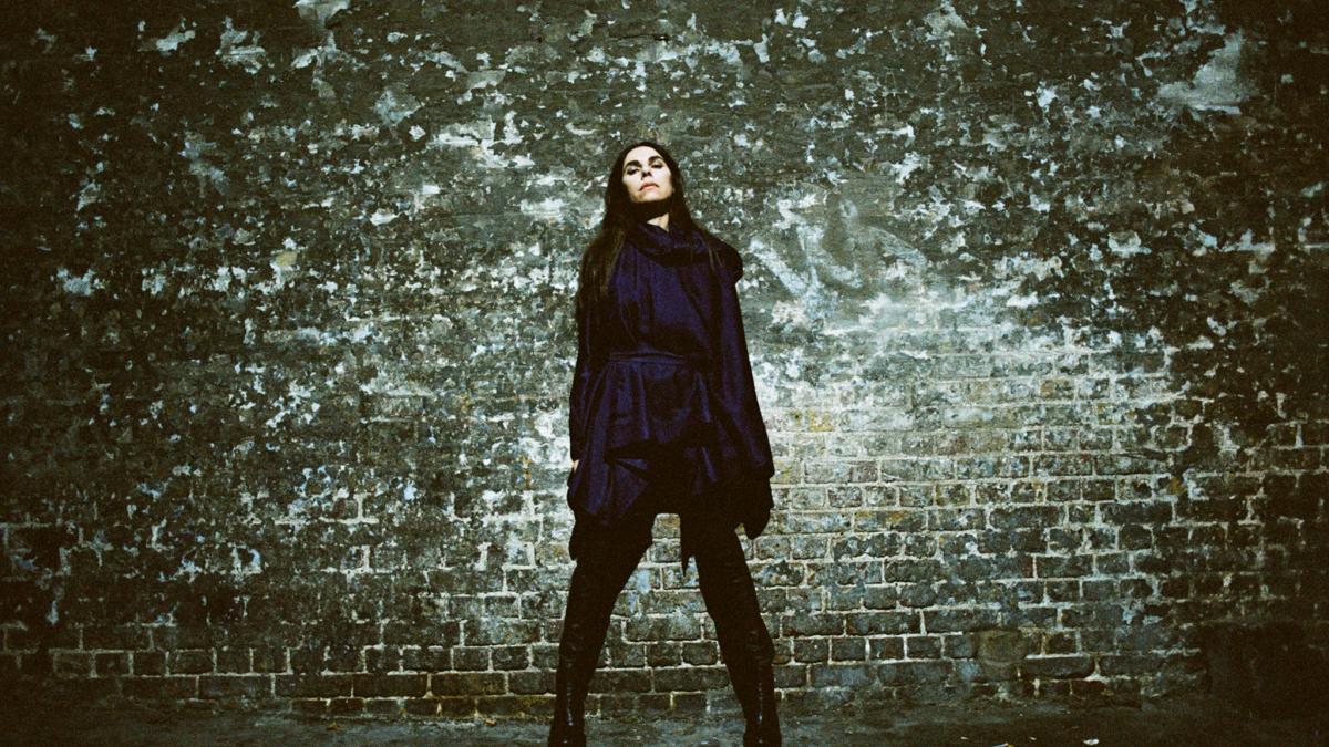 Kobieta w ciemnym stroju na tle zielonej ściany