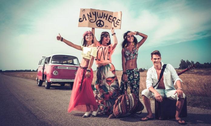 Dziewczyny w kolorych ubraniach łapią stopa, tabliczka z napisem