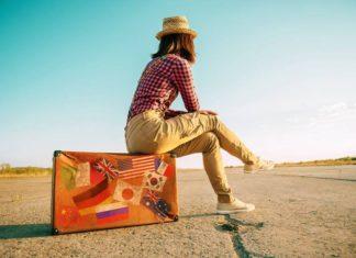 Mężczyzna w kapeluszu siedzi na korolowej walizce na piaszczystej drodze