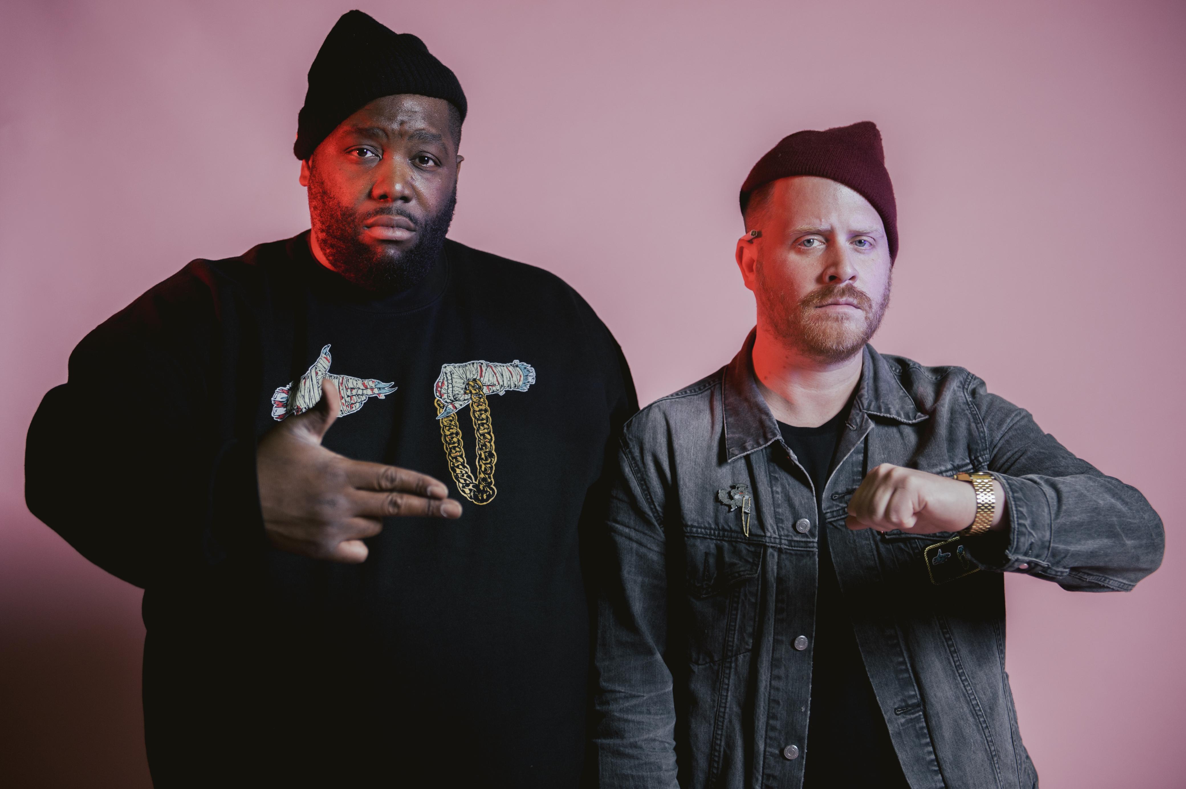 Dwóch raperów w czapkach, jeden jest czarnoskóry, drugi ma czerwoną czapkę i dżinsową kurtkę