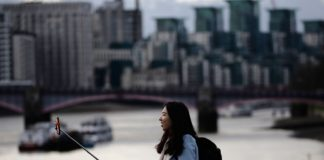 Brunetka w niebieskim płaszczu robi zdjęcie selfie stickiem