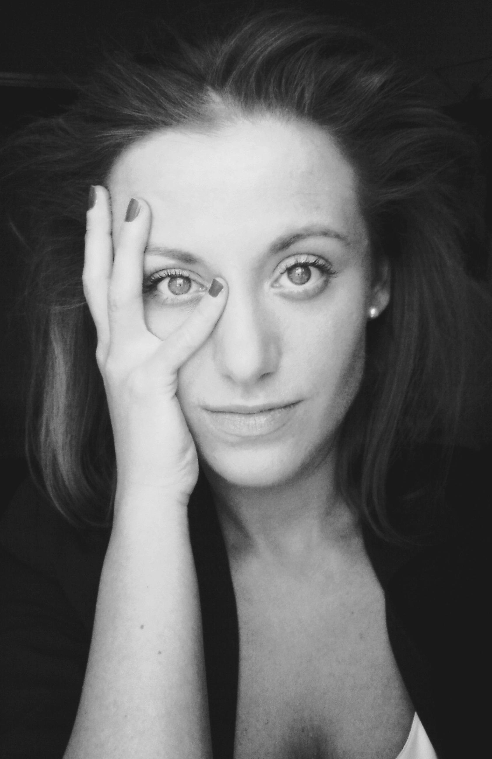 Kobieta w ciemnej bluzce z dłonią przy twarzy