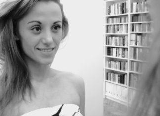 Kobieta z długimi włosami na tle półki z książkami