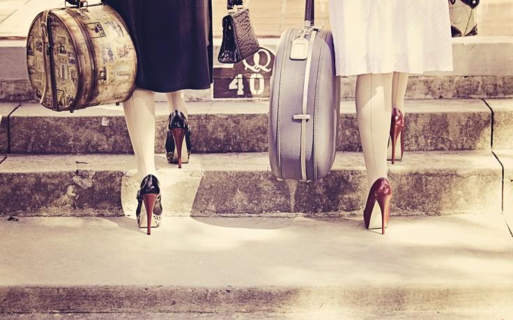 Kobiety w szpilkach z walizkami idą po schodach