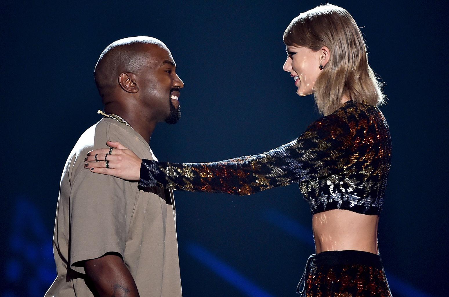 Blondynka w ciemnych ubraniach kładzie rękę na ramieniu czarnoskórego mężczyzny, który jest niższy od niej