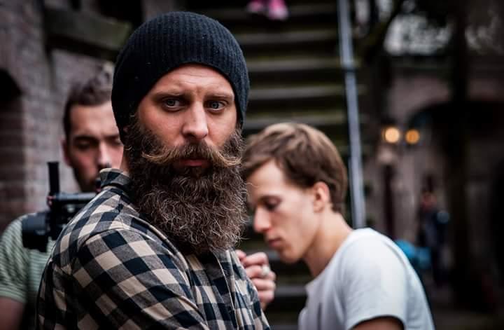 Mężczyzna z brodą w kraciastej koszuli i czapce